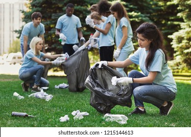 Volunteers picking up litter in dirty summer park. Ecology and environmentalism concept, copy space