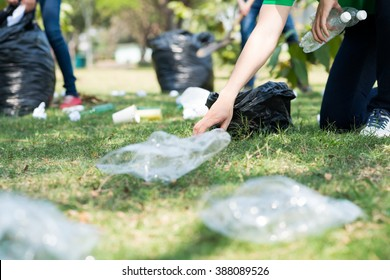 Volunteers picking up trash on a meadow