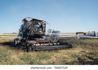 Volunteers put out a burning combine during harvest