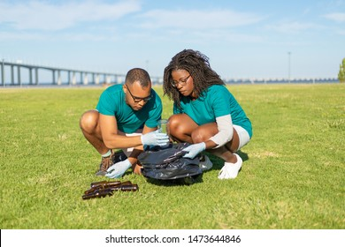 Volunteers removing empty bottles from grass to plastic bag. Black woman and Latin man wearing uniforms and protective gloves cleaning lawn from rubbish. Trash removal concept