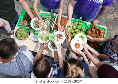 Volunteers serving food for poor people outdoors, top view