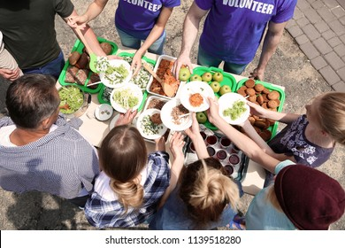 Volunteers serving food for poor people outdoors, above view