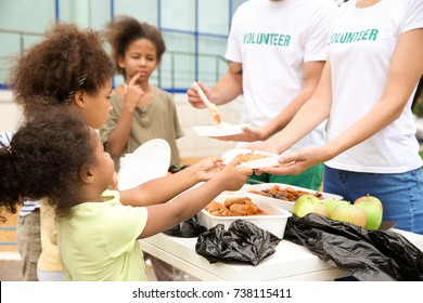 Volunteers sharing food with poor African children outdoors