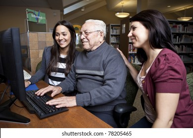 Volunteers teaching a senior how to use a computer