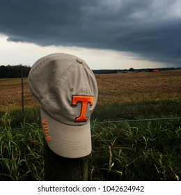 A Volunteers or Vols ball cap or hat from the University of Tennessee rests on a fence post in a rural setting. Storm clouds in background. Symbolic that a storm is coming.