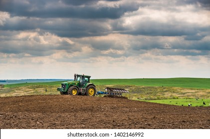 Volyn region, Ukraine, August 28, 2018; Agriculture. Tractor plows the field. Many birds around the plow.