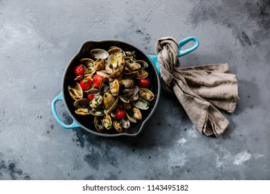 Vongole Seafood Clams with tomatoes and parsley in frying cooking pan on concrete background