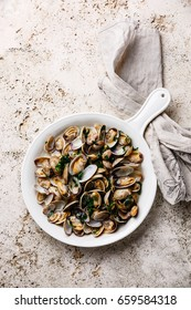 Vongole Shells Clams with parsley in white pan on travertine stone background