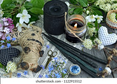 Voodoo doll, black candles, flowers and mysterious objects. Occult, esoteric and divination still life. Halloween background with vintage objects and magic ritual