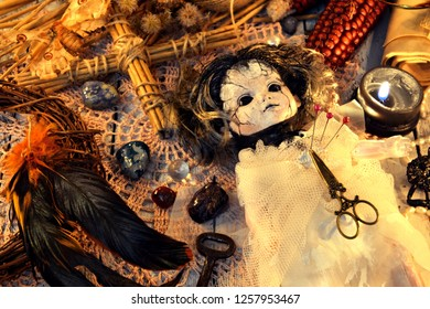 Voodoo doll in bride dress with rooster feathers, cross and black candle on lace napkin. Magic ritual. Wicca, esoteric and occult background with vintage witch objects
