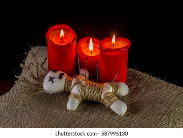 A voodoo doll and candles are on a table