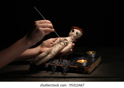 Voodoo doll girl pierced by a needle on a wooden table in the candlelight