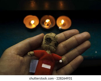 Voodoo doll on background with candles
