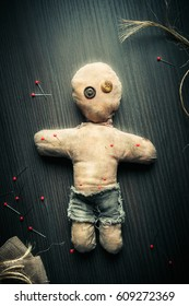 Voodoo Doll on a wooden background with dramatic lighting