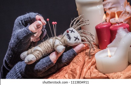 a voodoo doll is stung with needles at a ceremony