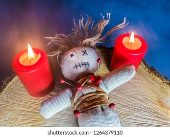 a voodoo doll and two red candles are on a tree slice