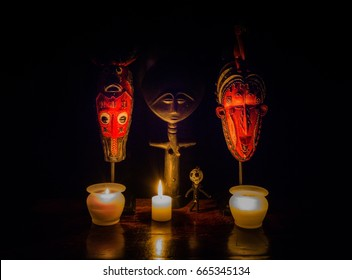 Voodoo Ritual - a stylized image depicting a voodoo ritual.  African masks, a fertility goddess, a voodoo doll and candles make for a striking image.