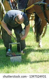 Vorden, The Netherlands - August 9th, 2015: Blacksmith repairs the hoof of a horse with a new hoof iron during the Castletour in Vorden, The Netehrlands