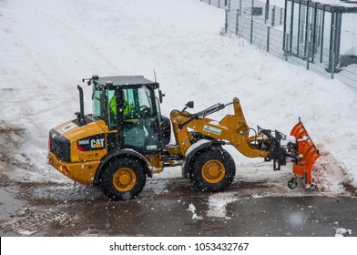 Vordingborg Denmark - February 3. 2018: Caterpillar wheel loader with a snowplow plowing snow during a blizzard