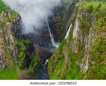 Voringsfossen waterfall, green summer mountains, Mabodalen canyon Norway. National tourist Hardangervidda route, touristroad Rv7, Eidfjord sightseeing tour.