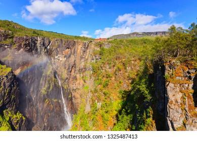Voringsfossen waterfall with rainbow in summer, Mabodalen valley Norway. National tourist Hardangervidda route, touristroad 7, Eidfjord sightseeing tour.