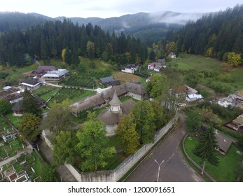 """Voronet Monastery, Romania, autumn view. One of famous Romanian painted Orthodox monasteries in southern Bucovina. UNESCO world heritage site.  Monastery known as """"Sistine Chapel of the East""""."""