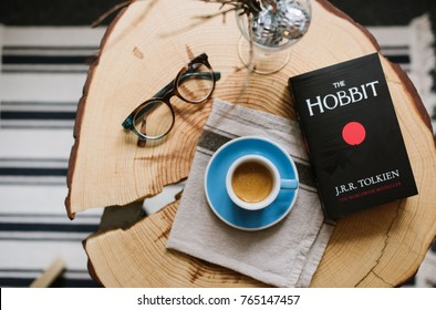 VORONEZH, RUSSIA, 11.29.2017: espresso coffee with beautiful crema, glasses, fancy Christmas decoration and the Hobbit book by J.R.R. Tolkien on hand made wooden pine slab table background