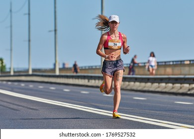 Voronezh, Russia - 24.08.2019 - Young girl runs along road. Runners marathon and championship competition, copy space. Street sprinting outdoors. Healthy sport event.