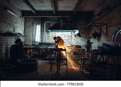 Voronezh, Russia - CIRCA December 2017: Worker cutting metal in dark workshop, sparks fly, industrial work with steel