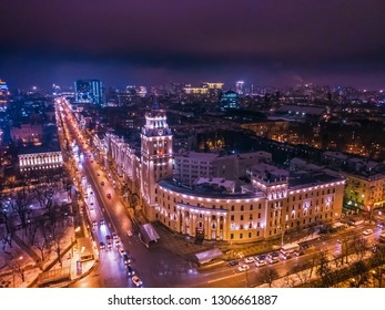 Voronezh, Russia - Circa February 2019: Arial view of Voronezh Main South-Eastern Railway Building tower in night, symbol of Voronezh and evening cityscape with rads, parks and traffic, drone shot
