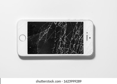 Voronezh, Russia. December, 25, 2019.  Modern smartphone with seriously broken display screen isolated on white background. Device needs repair.