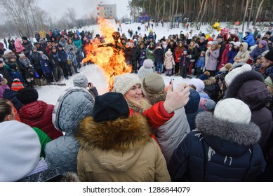 VORONEZH, RUSSIA - FEBRUARY 21 2015: Unidentified woman takes selfie on a background of burning dummy at the festival Maslenitsa in Voronezh, Russia. Maslenitsa is very popular in Russia.