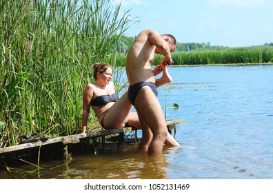 Voronezh, Russia, July 2016:Young man and young woman relaxing on the river bank.  The guy heals the leg girl.
