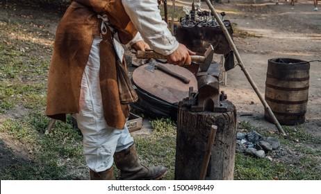 Voronezh, Russia September 5, 2019: Senior blacksmith forging the molten metal on the anvil in smithy. Blacksmithing. Hammer and anvil. Blacksmith forging iron. Village craft. Blacksmith working metal
