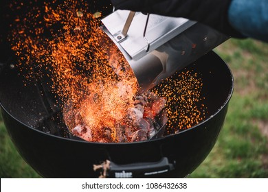 VORONEZH/RUSSIA-04.30.2018: Fire sparks caught up in the moment of putting hot wood charcoal from the fire starter into the weber GBS charcoal barbecue grill, close up view