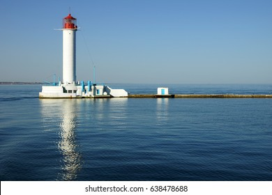 The Vorontsov Lighthouse reflects on blue water. Famous red-and-white, 27.2 metre landmark in the Black Sea port of Odessa, Ukraine.