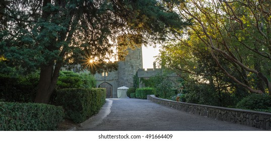 Vorontsov palace park, Alupka, Crimea. Turret and fortress wall with a gate. Sun shines through the green foliage. Scottish Baronial, Mughal architecture,  Gothic Revival architecture styles.