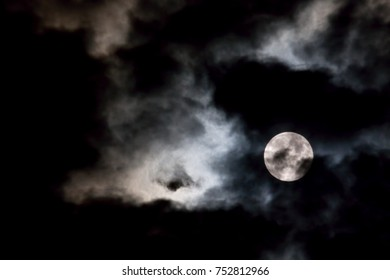 Vortex of eerie white clouds and full moon against a black night sky