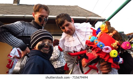 VORTOVA, CZECH REPUBLIC – FEBRUARY 25, 2017: A young boy smiles as a man shows him his Masopust mask. All ages take part in this pre-Lenten Shrovetide celebration in the Czech town of Vortova.