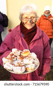 VORTOVA, CZECH REPUBLIC – FEBRUARY 25, 2017: A woman serves sugar-dusted buns at Masopust, a UNESCO-listed Pre-Lenten Shrovetide carnival celebration. Attendees receive black marks on their face.