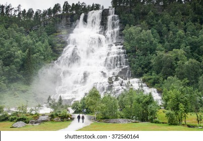 Voss, Norway - August 16, 2015: people walking to Tvindefossen waterfall on a rainy day. The water has a reputation for rejuvenation and revival of sexual potency .
