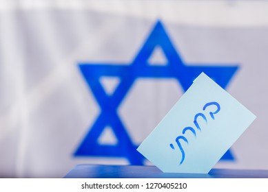 Vote box on election day. Hebrew text I voted on voting paper over Israel flag background. Freedom Democracy Concept.