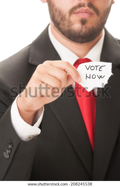 Vote Now concept using a politician wearing a black suit and red necktie and holding a piece of paper with the text vote now on it.
