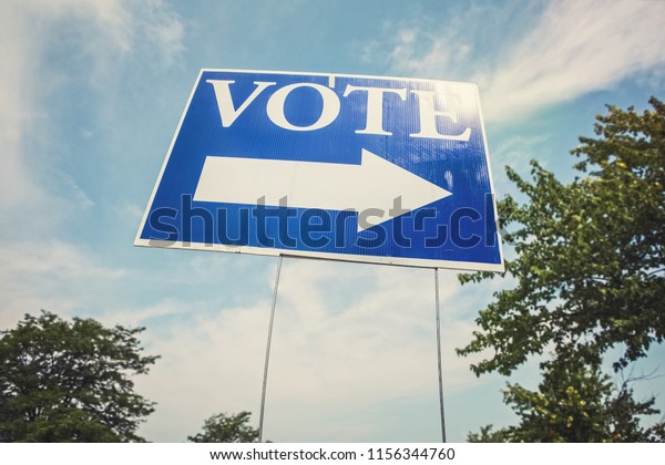 Vote sign with arrow  against the sky with sun flare