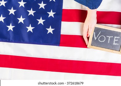 Vote sign on chalk board next to the American Flag.