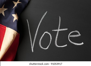 Vote sign on a chalkboard with vintage American flag