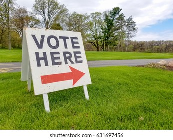 vote sign with red arrow on grass