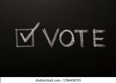 Vote tick on chalkboard, black background, elections 2020, patriotic concept
