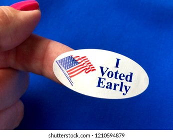 I voted early sticker on a woman's finger with blue background
