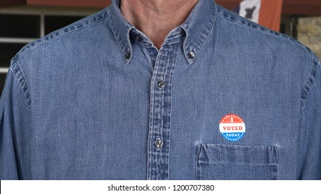 I Voted Today sticker on the shirt of a blue collar senior caucasian man for midterm elections in the USA